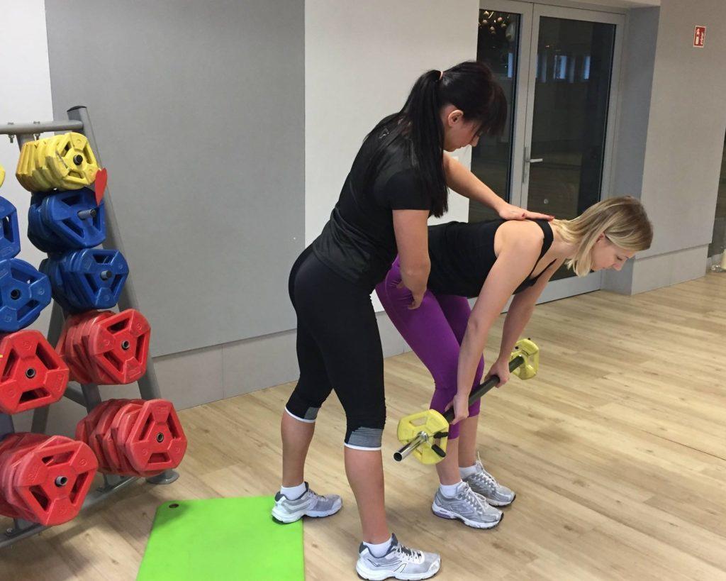 Na treningu indywidualnym w Poznaniu trener pokazuje jak prawidłowo wykonać ćwiczenie na plecy