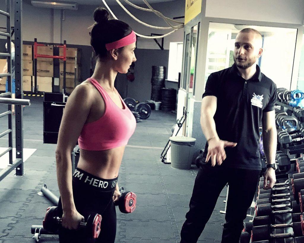 Trener osobisty w Poznaniu pokazuje jak poprawnie wykonać ćwiczenie