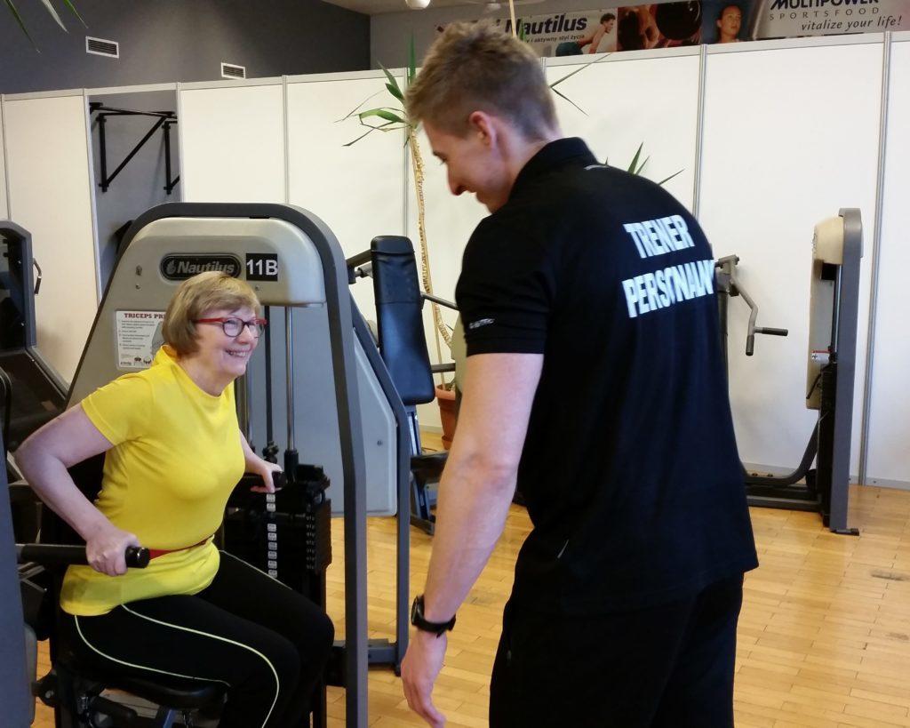 Trener personalny zwraca uwagę na poprawne wykonanie ćwiczenia